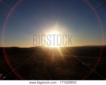 A sunset viewed from atop a hill with a mountain range in the background, encapsulated in a perfectly positioned circular lense flaire.
