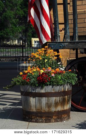 Old wooden barrel serves as a planter for beautiful flowers. Barrel sits in front of the Old Train Depot in Livingston Montana.