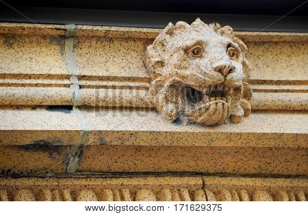 Cracked and aging eaves of old train depot has lion's head decoration. Train depot is in Livingston Montana.