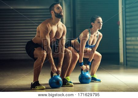 Fit man and woman training by kettlebell.