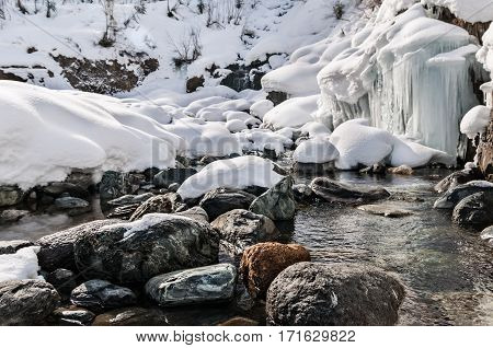 Winter landscape of mountain river with stones and small frozen waterfall.
