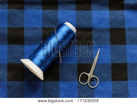 Blue threat with scissors on a blue lamberjack fabric