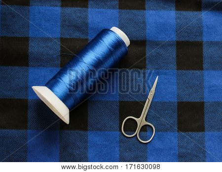 Blue threat with scissors on a colorful fabric