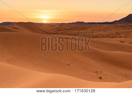 A beautiful sunset at the dunes of Ouzina located in the Sahara desert, Morocco.