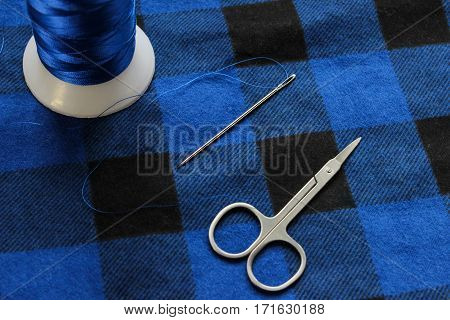Blue threat with steel scissors on fabric
