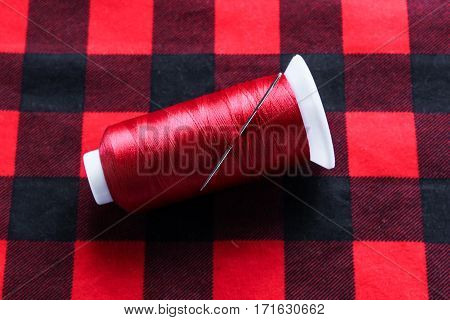 Red string with needle on colorful fabric