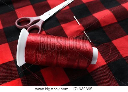 Red threat with needle and scissors on colorful fabric