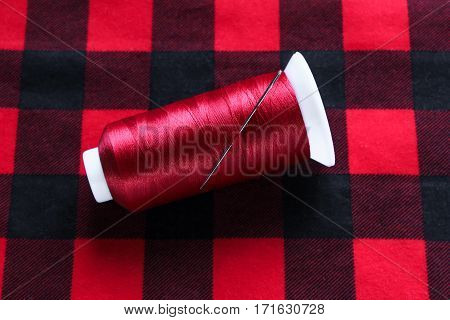 Red threat with needle on colorful fabric