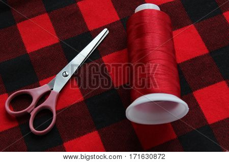 Scissors and threat lie on a red fabric