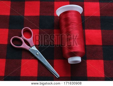 Scissors with threat lie on lumberjack fabric