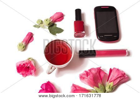 Red flowers nail polish lip gloss pink mobile phone are isolated on a white background flat lay top view.