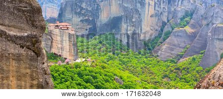 Panoramic view of Meteora monastery on the high cliff rock and road in the mountains at spring time, Greece