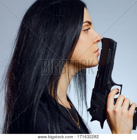 Pretty young gothic girl with gun over blue background