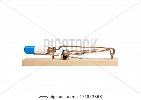 Drug capsule as bait in a mousetrap. Studio close-up isolated on white. Concepts could include addiction danger risk others.