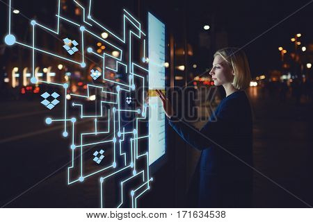 Young woman touching sensitive screen while selecting surface option. Female standing at big display with advanced innovative device with infographics design elements.Person with futuristic technology