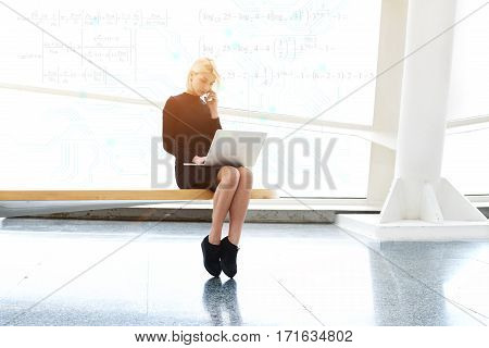 Pretty female with net-book on knees having cell telephone conversation. Student girl doing financial calculations using mathematical formulas in modern interior.Infographics equations design elements