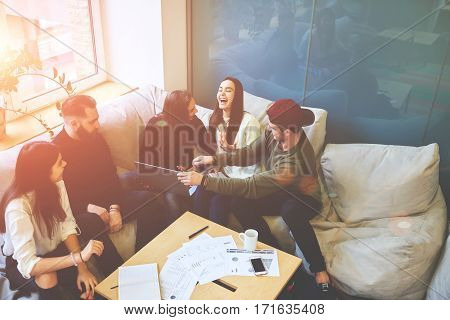 Having fun during preparing successful business project with skilled colleagues in friendly atmosphereusing digital devices and internet. University students working on coursework joking in coworking