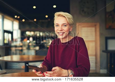 Cheerful casual dressed female hipster use touch pad for sharing multimedia files on web page while spending leisure time in cafe sitting near copy space for your advertising content or text messages