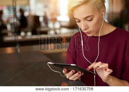Hipster woman shares multimedia files texting messages in online chat while listening to music via touchpad using fast 4G connection to internet sitting in coffee shop. Copy space for advertising
