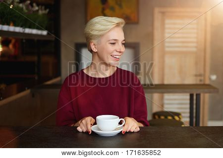 Young hipster girl with short haircut having fun during coffee break in modern coffee shop. Attractive woman dressed in trendy clothing with copy space area for your brand name or advertising script