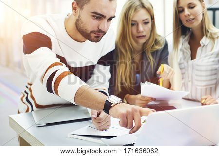 On frontage professional media coach pointing mistakes in students pres-release published on web page while on blurred background two young female pupils listening explanation making notes with pen