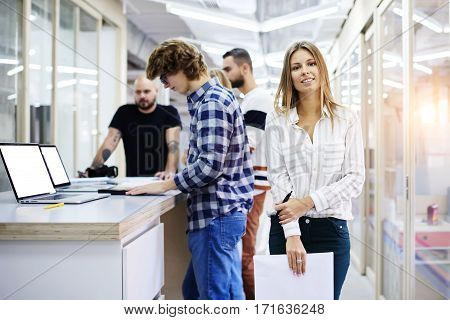 Portrait of young female team leader of talented journalists organizing work of members motivates and inspire them to make researching standing on blurred background in modern coworking space