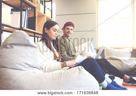 Young male and female classmates preparing for upcoming exam testing on modern marketing strategy reading literature using laptop and internet connection sitting in university coworking space