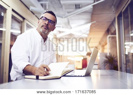 Male skilled jurist writing notes after consultancy with client. Mature editor creating new magazine article by using notebook and laptop computer. Experienced manager developing work-sharing plan