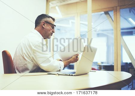 Experienced businessman using laptop while working on a document in his office. Stock broker making deals while reviewing exchange statistics. Executing director prepares for the meeting with partners