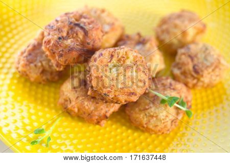 Fried cabbage kofta on yellow plate-typical Indian food.