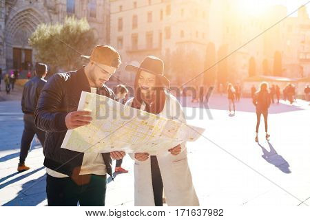 Sweet young couple using the map in Barcelona center Stylish hipster girl with her boyfriend using touristic guide during walk in historic center of the city.Young couple in love spend their honeymoon poster