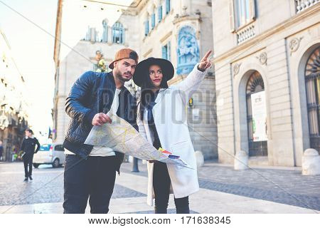 Young tourist couple walking in Barcelona city at sunny day. Hipster man and his pretty girlfriend using the map for visit historical attractions.The newlyweds making a honeymoon journey in Spain.