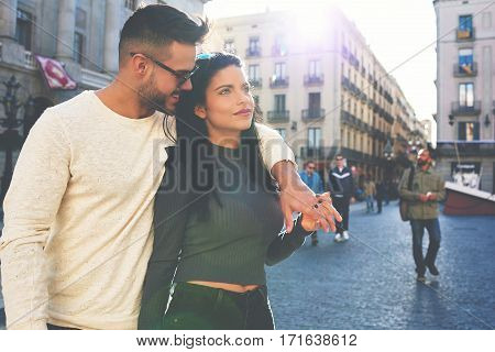Cute romantic couple walking in city center of Barcelona. Stylish hipster guy enjoying a romantic date with a girl in love. Beautiful lovers strolling in Europe old town during their vacation travel