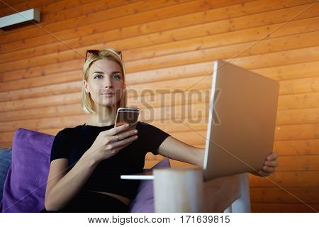 Young woman is thinking what to write is text message on cell telephone while is sitting with net-book in co-working space. Hipster girl is waiting call on smart phone during work on laptop computer