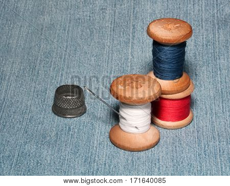 sewing spools with colorful threads and needles metal thimble lie on denim background