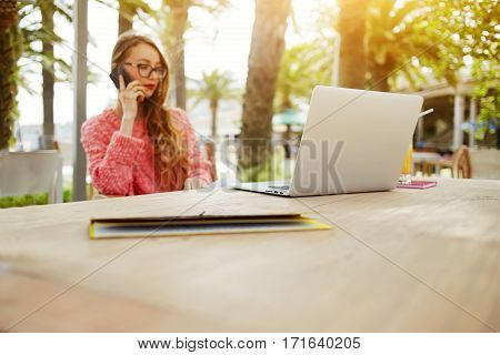 Young female student is calling with mobile phone while is sitting in cafe outdoors at the table with laptop computer. Pretty business woman having cell telephone conversation after work on net-book