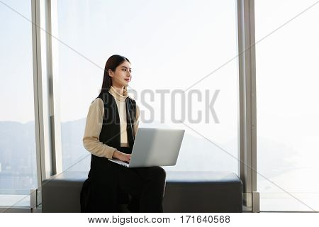 Japanese businesswoman with laptop computer on knees is looking on her international partners what she expect in her big successful company in Honk Kong.Young female manager is using portable net-book