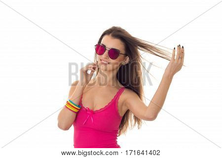 cutie young lady with dark hair in pink summer shirt and sunglasses smiling isolated on white