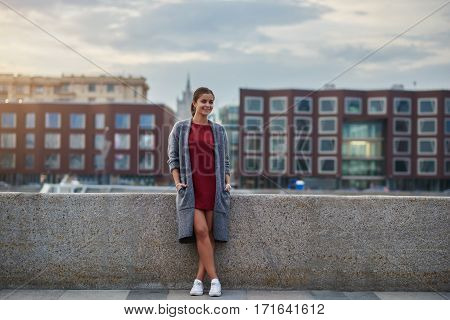 Young woman with beautiful smile dressed in cool fashionable clothes is standing near river pier against blurred old buildings with copy space during her long awaiting spring weekend to St. Petersburg