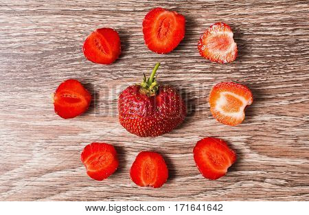 The texture of a whole and cut red ripe strawberries on wooden background. Summer ripe berries.
