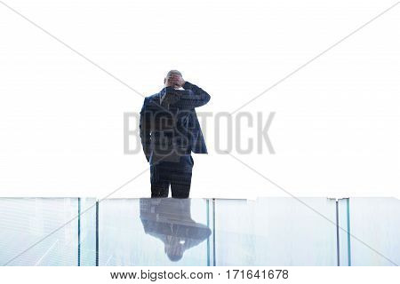 Back view of man economist having headache after analyzing and detection of the causes of loss of profitability of the enterprise while is standing in his office near big window with double exposure