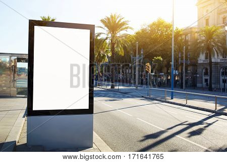 Blank billboard with copy space for your text message or content outdoors advertising mock up public information board on city road flare sun light. Empty Lightbox on urban setting sidelines