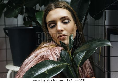 Beautiful Young Woman With Large Green Leafs In Faux Eco Fur Coat Over White Checkered Background.
