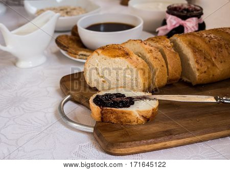 Sliced loaf of bread with currant jam with jar cup of tea on background. Healthy breakfast