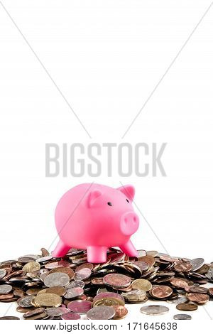Piggybank bank standing on a pile of coins with copy space