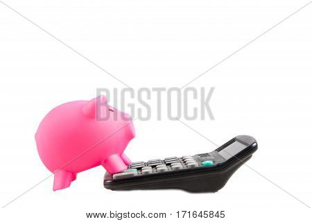 Piggybank with front feet standing on a calculator
