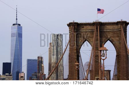 in the foreground the pillar of the bridge with the american flag in the background the skyscrapers of Manhattan