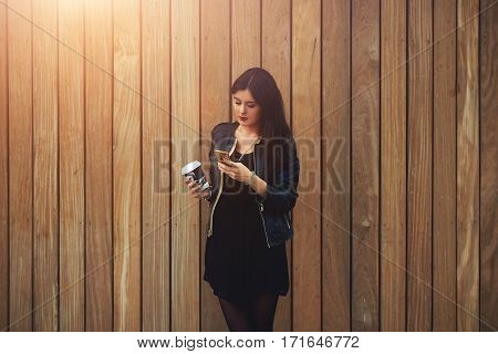 Beautiful female with take away coffee in hands typing text message to friend using a mobile phone. Young woman reading news on cellular while standing near background where you can insert advertising