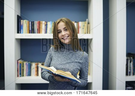 Portrait of cheerful beautiful young female pupil reading manual book while making researches of information for coursework spending free time in modern university library searching right textbook
