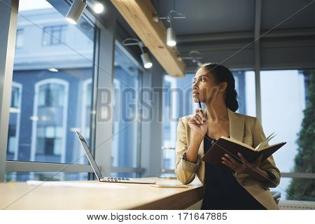 Skillful professional female thinking over organizing work in office and employee while being in business trip waiting for meeting with partners using laptop and wireless connection in coworking space